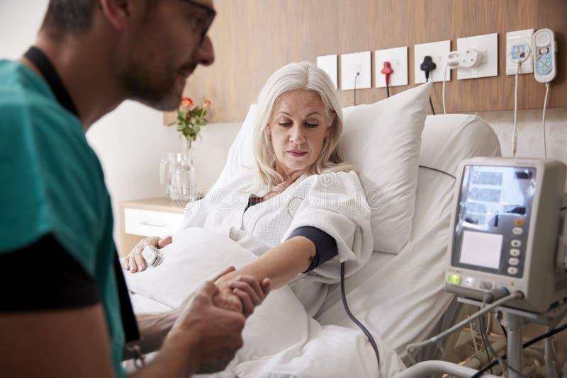 Męska pielęgniarka Bierze Dojrzałym Żeńskim pacjentom ciśnienie krwi W łóżku szpitalnym Z Automatyzującą maszyną zdjęcie royalty free