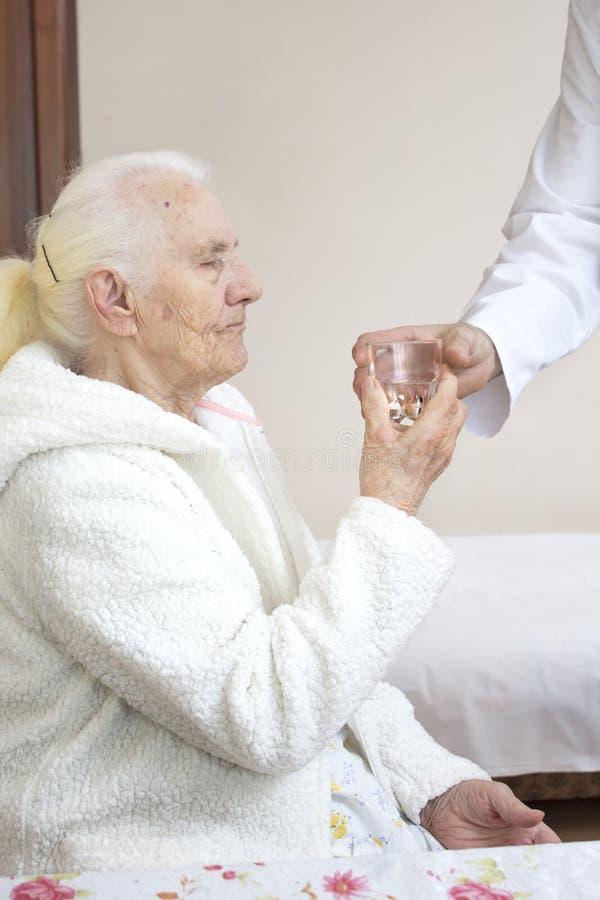 Męska pielęgniarka daje szkłu woda stara kobieta podczas lekarstwa zdjęcia stock