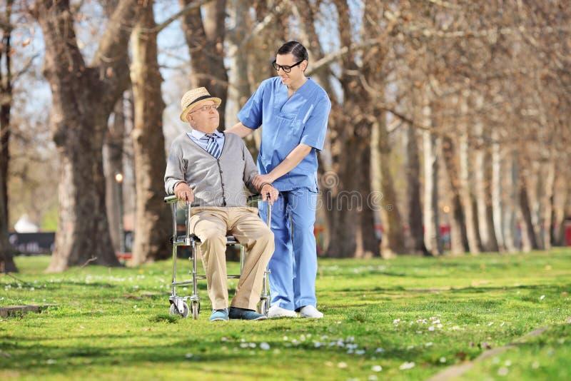 Męska pielęgniarka opowiada starszy mężczyzna w parku obrazy royalty free
