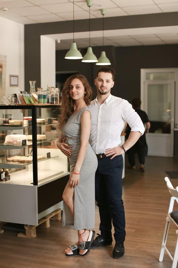 Męska przystojna kelnera i kobiety administratora pozycja przy kawiarnią zdjęcie royalty free
