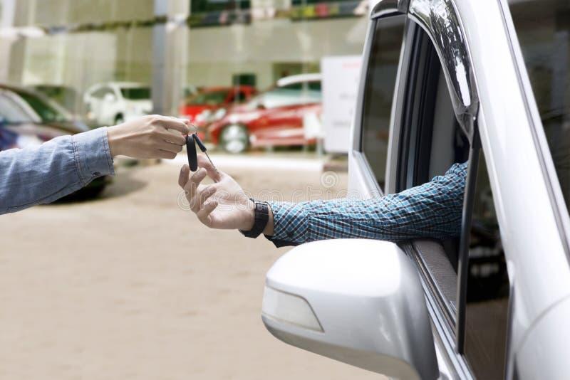 Męska ręka daje samochodowemu kluczowi obraz stock