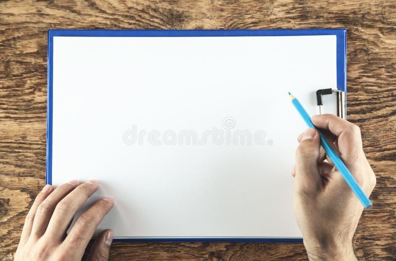 Męska ręka jest gotowa dla rysować z błękitnym ołówkiem fotografia stock