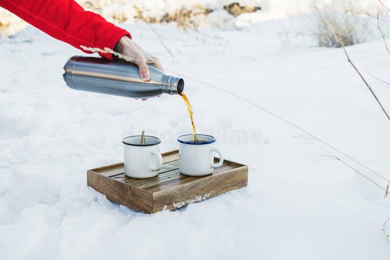 Męska ręka nalewa gorącą kawę lub herbaty w emaliową filiżankę na drewnianym pudełku outdoors zdjęcia stock