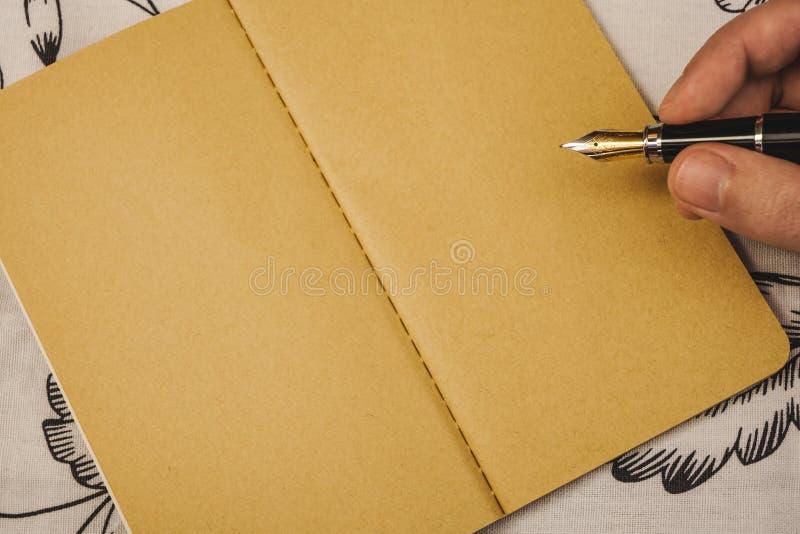 Męska ręka pisze z fontanny piórem na Kraft papieru notatniku Specjalne wydarzenie lub okazja z kopii przestrzenią zdjęcia royalty free