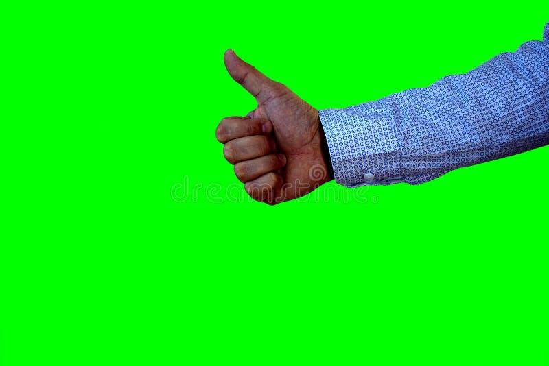 Męska ręka pokazuje jego kciuk up odizolowywającego na zieleni Positivity pojęcie zdjęcia stock