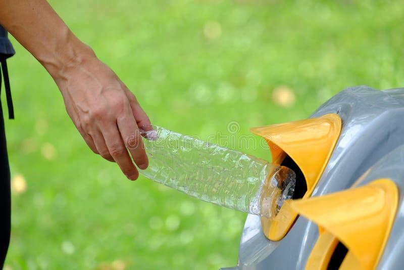 Męska ręka rzuca plastikowego butelka grat w przetwarzającego kosz na śmieci przy jawnym parkiem fotografia royalty free