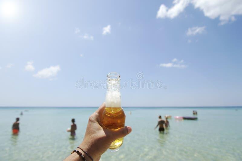 Męska ręka trzyma butelkę piwo przeciw niebu pogodnemu kryształowi i - jasny morze W tle niektóre ludzie ma zabawę w zdjęcie royalty free