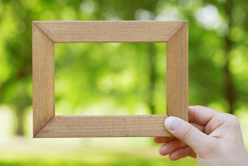 Męska ręka trzyma drewnianą ramę przeciw zamazanemu naturalnemu tłu Opróżnia przestrzeń dla teksta Łączyć z natury pojęciem zdjęcie royalty free