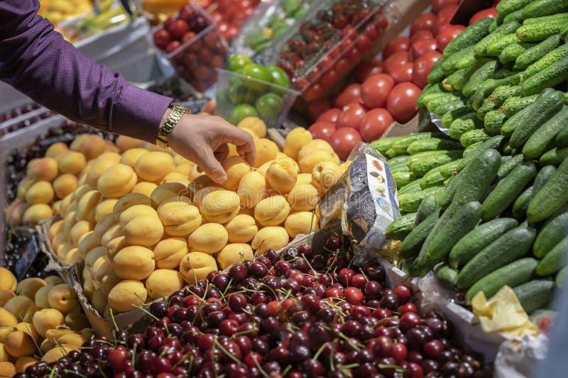Męska ręka trzyma nad kontuarem z świeżej owoc zakończeniem w karmowym rynku obraz stock