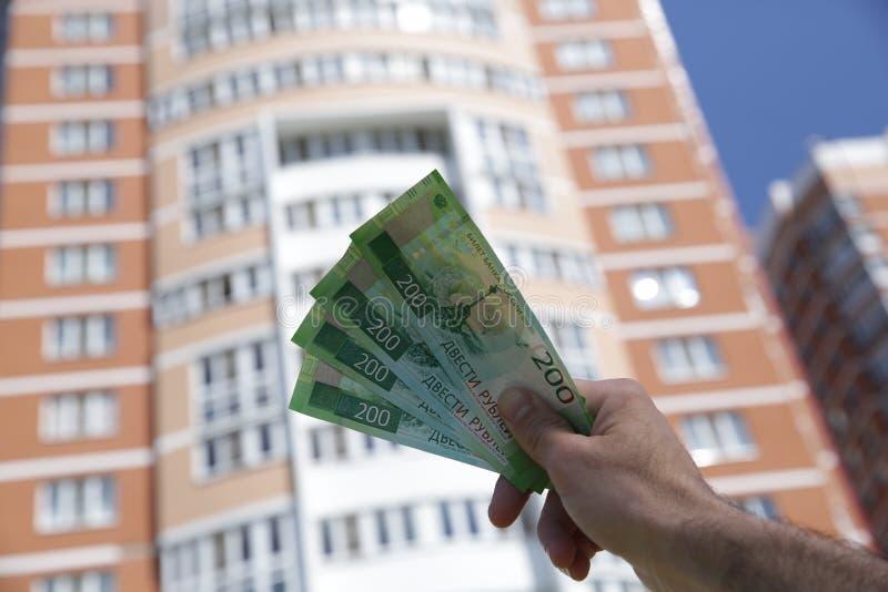Męska ręka trzyma nowego Rosyjskiego banknot dwieście rubli na tle duży budynek niebieskie niebo i Got?wkowy papierowy pieni?dze zdjęcia royalty free