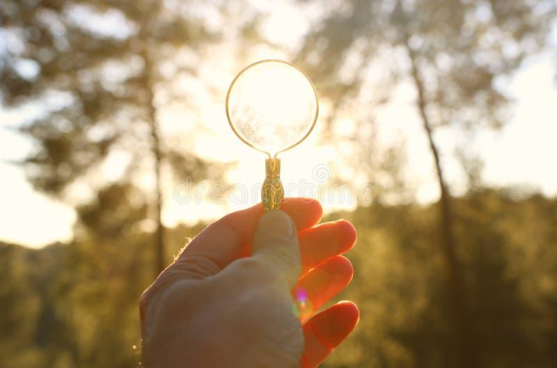 Męska ręka trzyma powiększać przeciw położenia słońcu outside - szkło pojęcie rewizja, kreatywnie główkowanie i używa energia sło obrazy stock