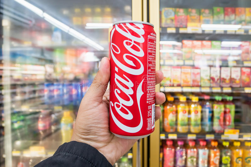 Męska ręka trzyma puszkę koka-kola w sklepie wielobranżowy obrazy stock