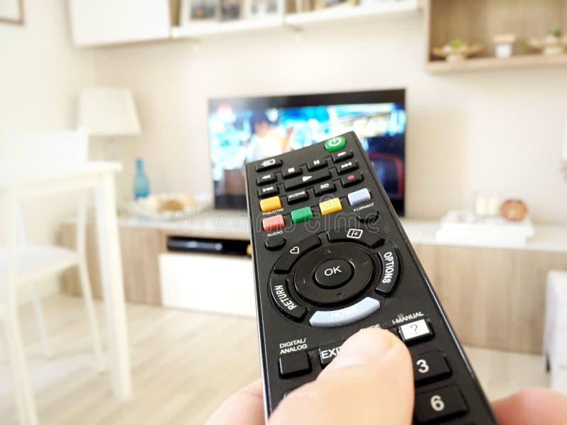 Męska ręka trzyma TV pilot do tv obraz stock