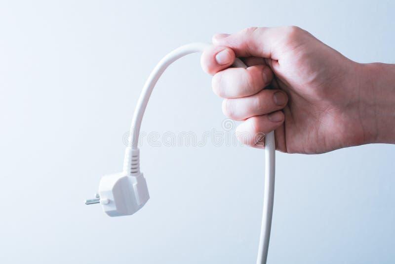 Męska ręka Trzyma władza kabel - oszczędzanie energii pojęcie obrazy stock