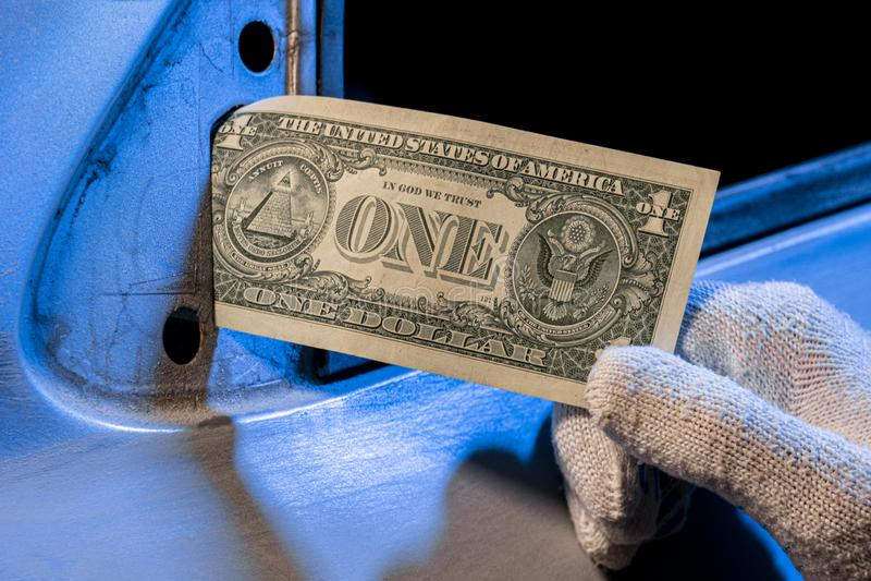 Męska ręka w białej rękawiczce trzyma jeden dolar zamiast lustra na drzwiach samochodu Ubóstwo i tanie płace w przemyśle motoryza zdjęcia stock