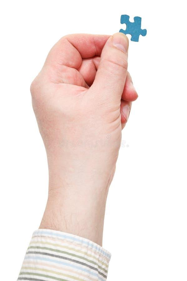 Męska ręka w koszulowym mienie wyrzynarki łamigłówki kawałku fotografia royalty free