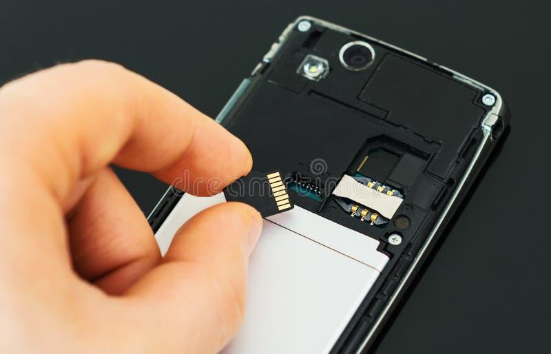 Męska ręka wkłada mikro SD zdjęcie royalty free