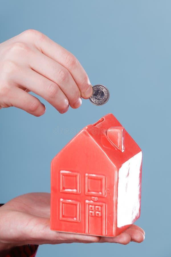 Męska ręka z małym domem i srebną monetą zdjęcia stock