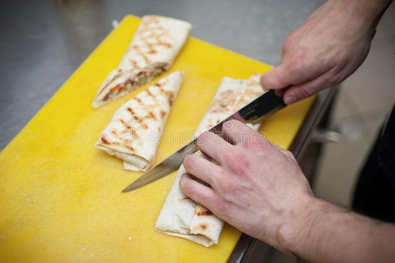 Męska ręka z nożową tnącą burrito rolką zdjęcie royalty free