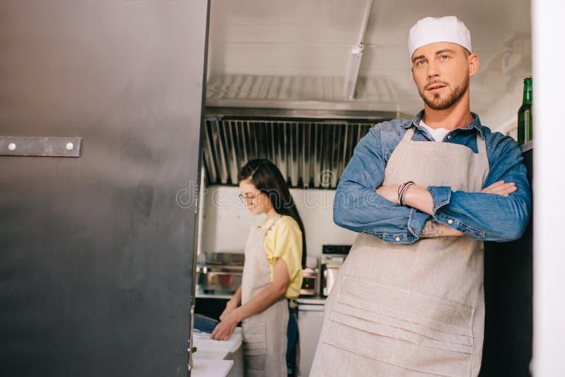 męska szef kuchni pozycja z krzyżować rękami podczas gdy żeński kolega pracuje za fotografia stock