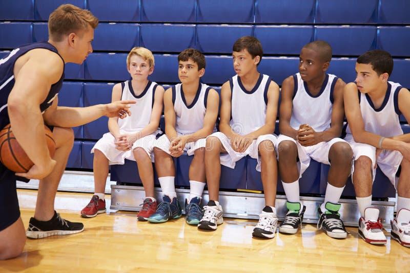 Męska szkoły średniej drużyna koszykarska Ma Drużynową rozmowę Z trenerem zdjęcie royalty free