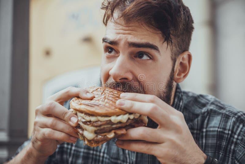 Męski łasowanie hamburger obraz royalty free