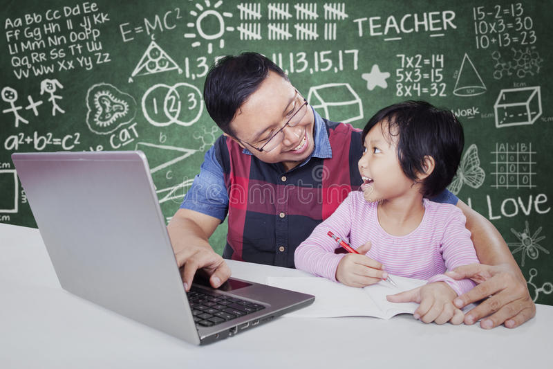 Męski adiunkt pomaga żeńskiego ucznia studiowaniu obrazy stock