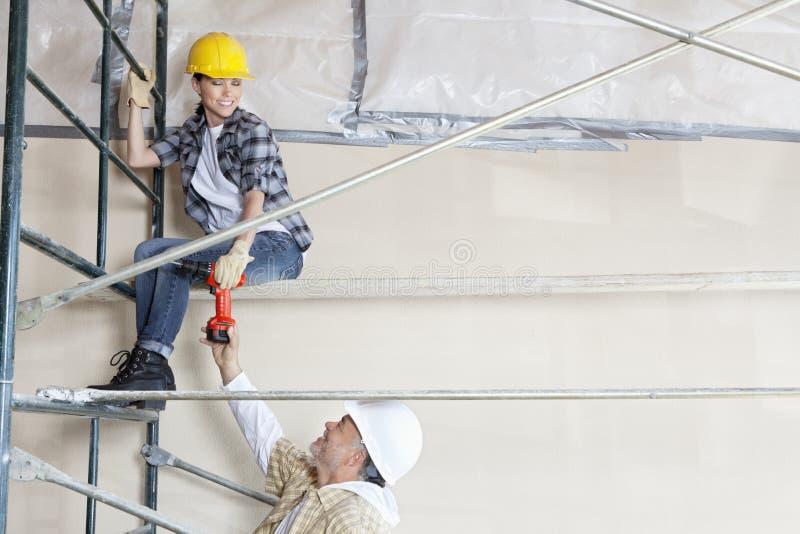 Męski architekt daje świderowi żeński pracownik na szafocie przy budową fotografia royalty free