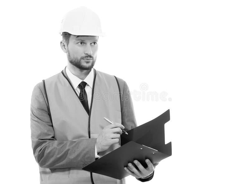 Męski architekt w zbawczym zachodzie i hardhat writing na jego cli zdjęcie stock