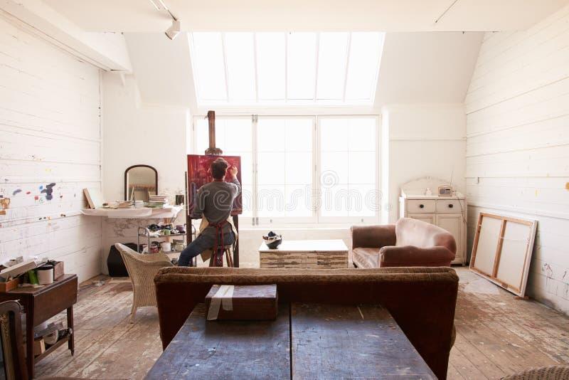 Męski artysta Pracuje Na obrazie W Jaskrawym światła dziennego studiu obrazy stock