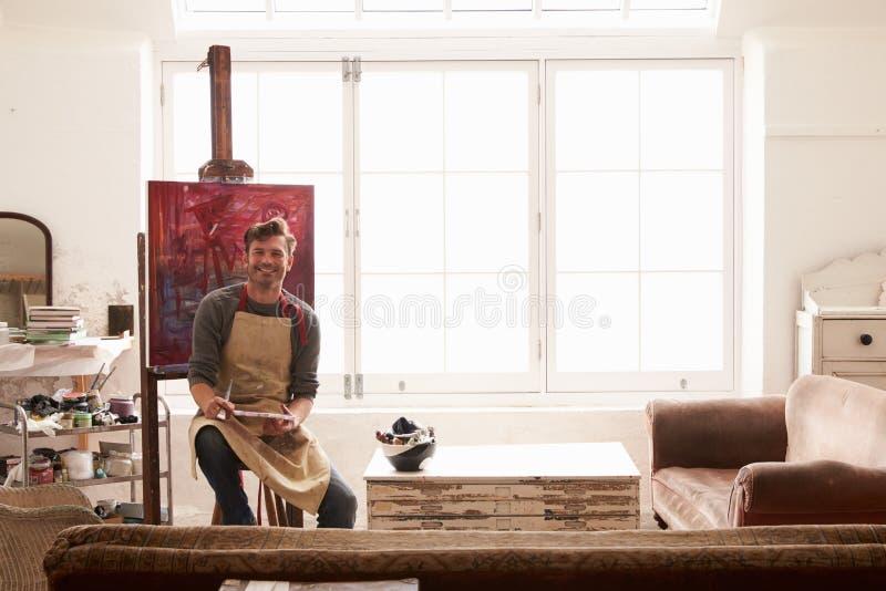 Męski artysta Pracuje Na obrazie W Jaskrawym światła dziennego studiu obrazy royalty free