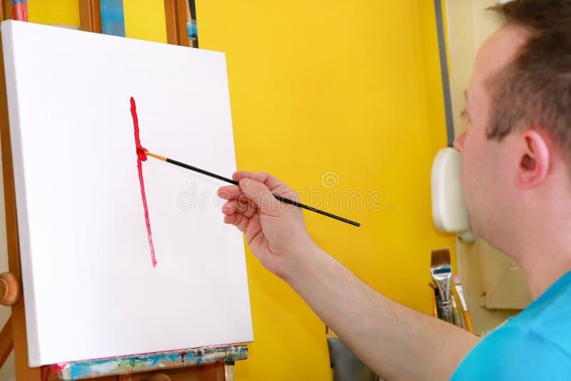 Męski artysty malarz pracuje w warsztacie z kanwą na drewnianej rysownicy sztaludze w sztuki farby studiu Portret artysta zdjęcie stock