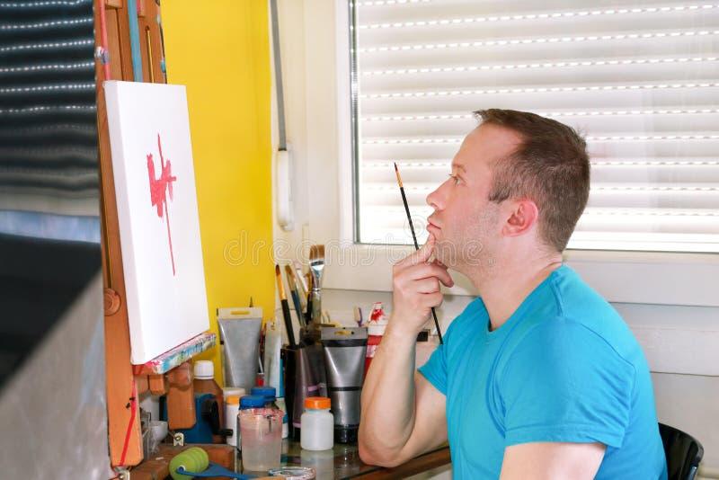 Męski artysty malarz pracuje w warsztacie z kanwą na drewnianej rysownicy sztaludze w sztuki farby studiu Portret artysta obraz royalty free