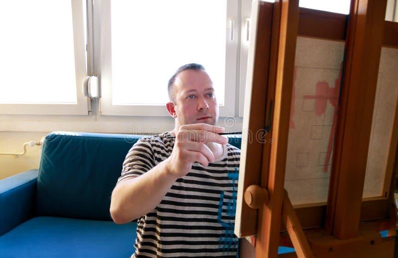 Męski artysty malarz pracuje w warsztacie z kanwą na drewnianej rysownicy sztaludze w sztuki farby studiu Portret artysta fotografia royalty free