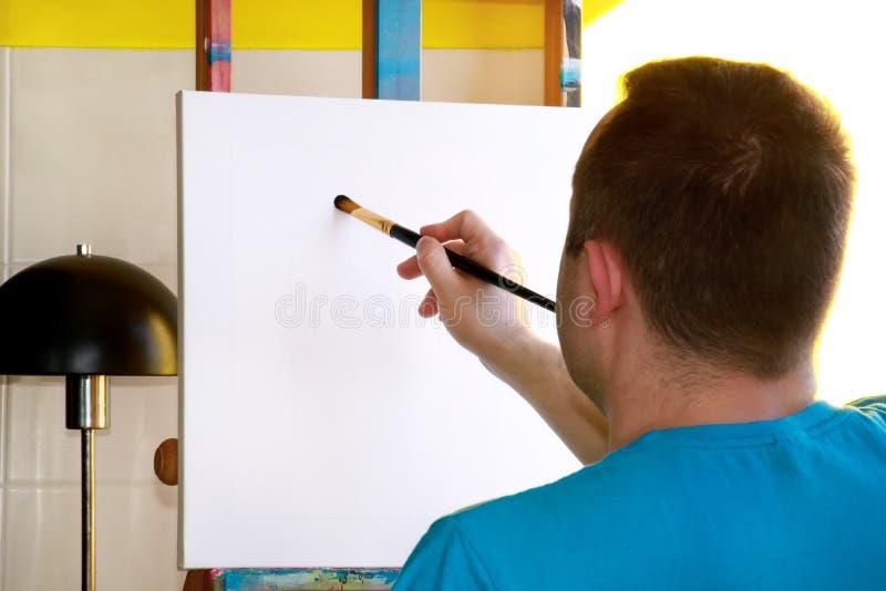 Męski artysty malarz pracuje w warsztacie z kanwą na drewnianej rysownicy sztaludze w sztuki farby studiu Portret artysta zdjęcia stock