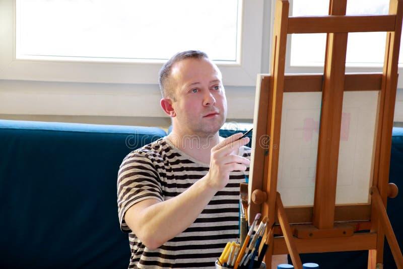 Męski artysty malarz pracuje w warsztacie z kanwą na drewnianej rysownicy sztaludze w sztuki farby studiu Portret artysta obrazy royalty free