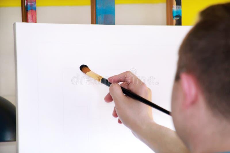 Męski artysty malarz pracuje w warsztacie z kanwą na drewnianej rysownicy sztaludze w sztuki farby studiu Portret artysta zdjęcia royalty free