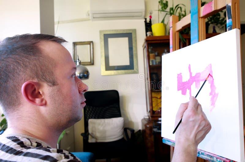 Męski artysty malarz pracuje w warsztacie z kanwą na drewnianej rysownicy sztaludze w sztuki farby studiu Portret artysta obrazy stock