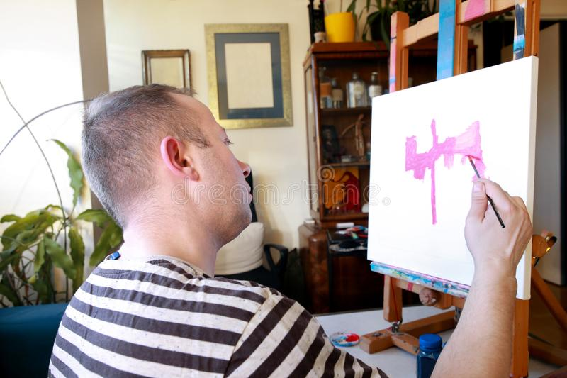 Męski artysty malarz pracuje w warsztacie z kanwą na drewnianej rysownicy sztaludze w sztuki farby studiu Portret artysta zdjęcie royalty free