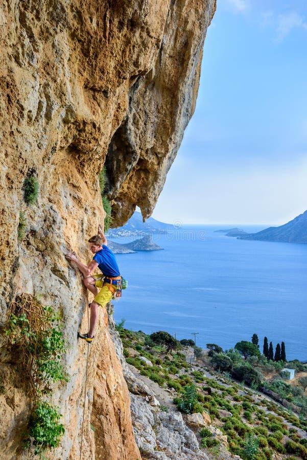 Męski arywista na nawisłym skała łuku, piękny widok wybrzeże fotografia stock