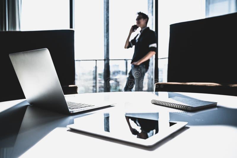 Męski Azjatycki małego biznesu właściciel używa telefonu komórkowego wezwanie w nowożytnym biurze z laptopem Zarządzanie projekte zdjęcia royalty free