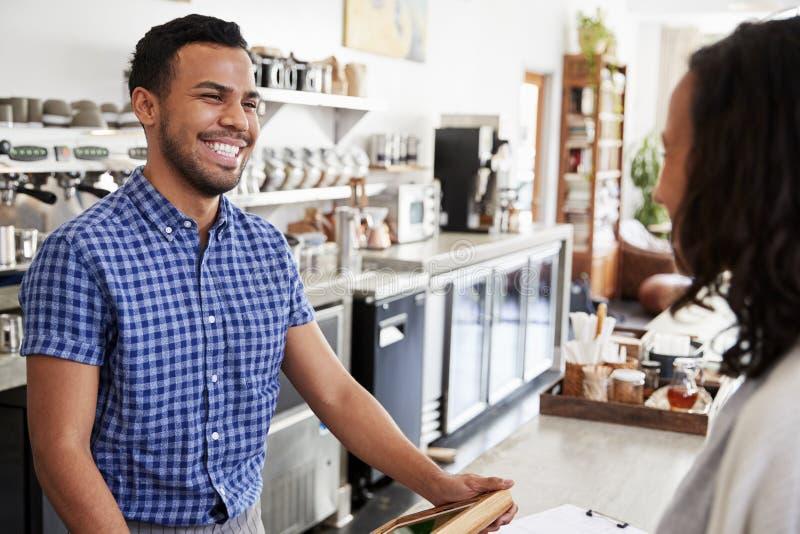 Męski barista ono uśmiecha się przy żeńskim klientem w sklep z kawą fotografia royalty free