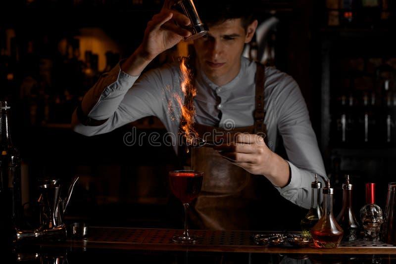 Męski barman dodaje pikantność dla wystroju w ogieniu nad wyśmienicie czerwony koktajl w szkle fotografia stock