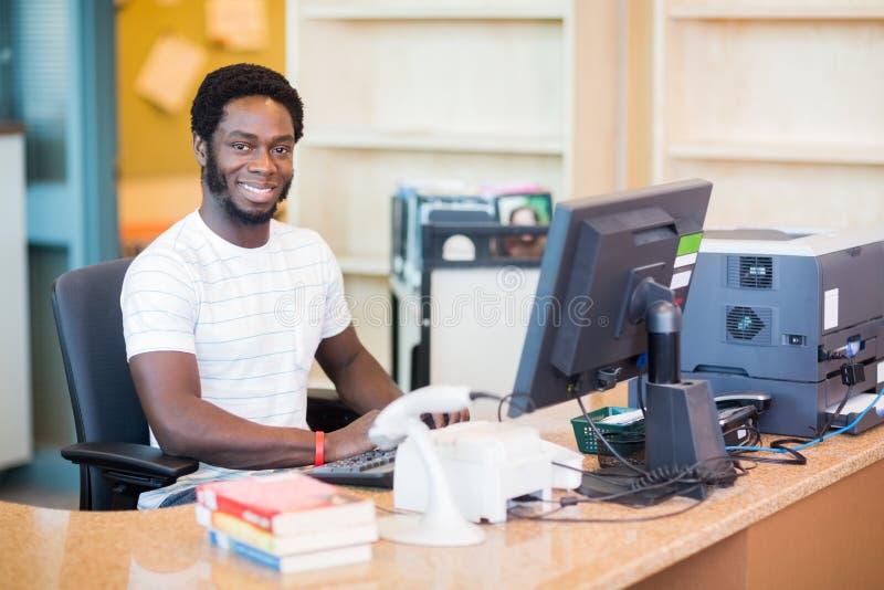 Męski Bibliotekarski działanie Przy biurkiem fotografia royalty free