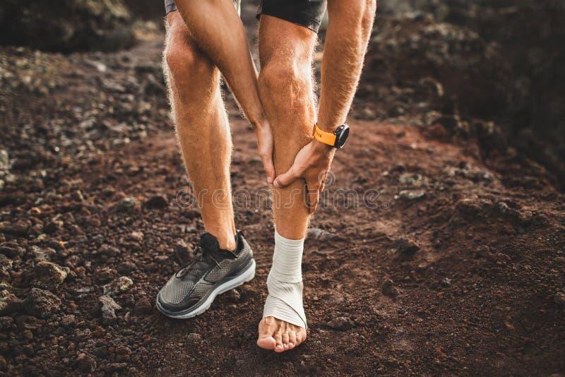 Męski biegacza mienie raniący bandażujący nogę w górę zdjęcia stock