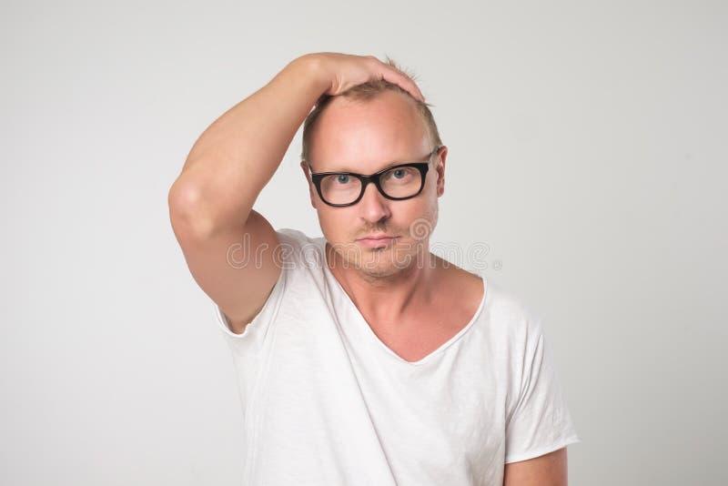 Męski blogger jest ubranym widowiska i biała koszulka, patrzeje pewnie fotografia stock