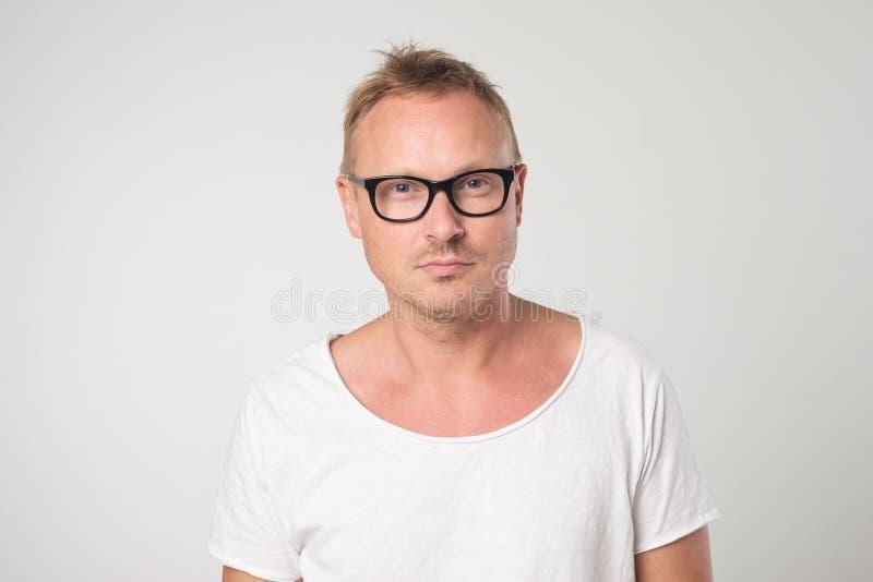 Męski blogger jest ubranym widowiska i biała koszulka, patrzeje pewnie zdjęcie stock