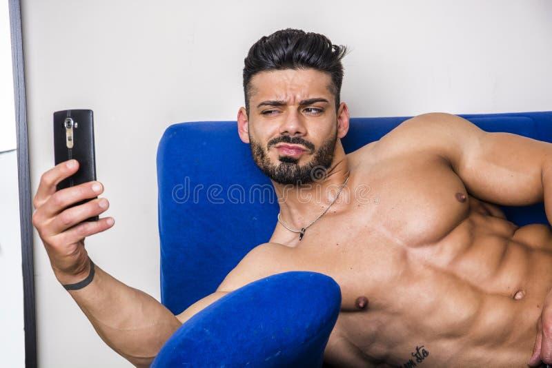 Męski bodybuilder bierze selfie fotografię na kanapie zdjęcia stock