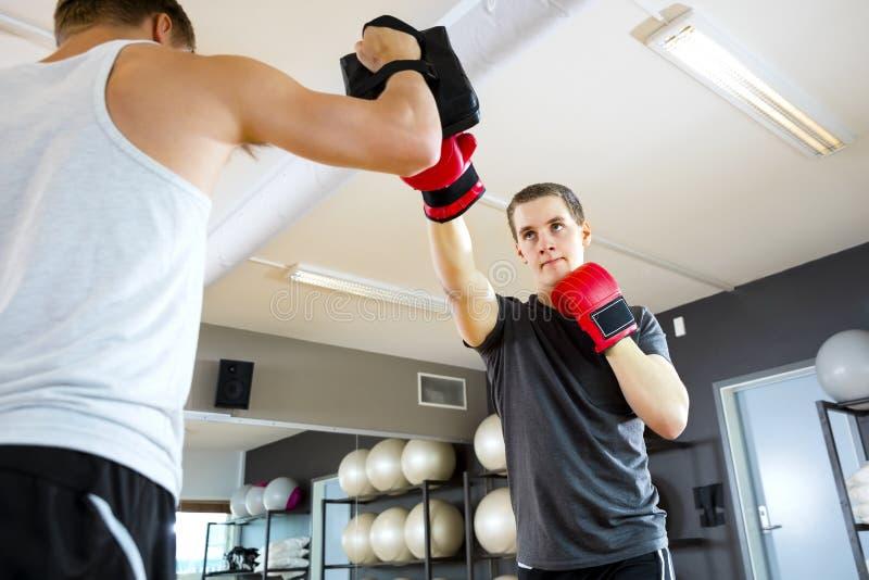 Męski bokser Uderza pięścią torbę Trzymającą instruktorem W Gym zdjęcie stock