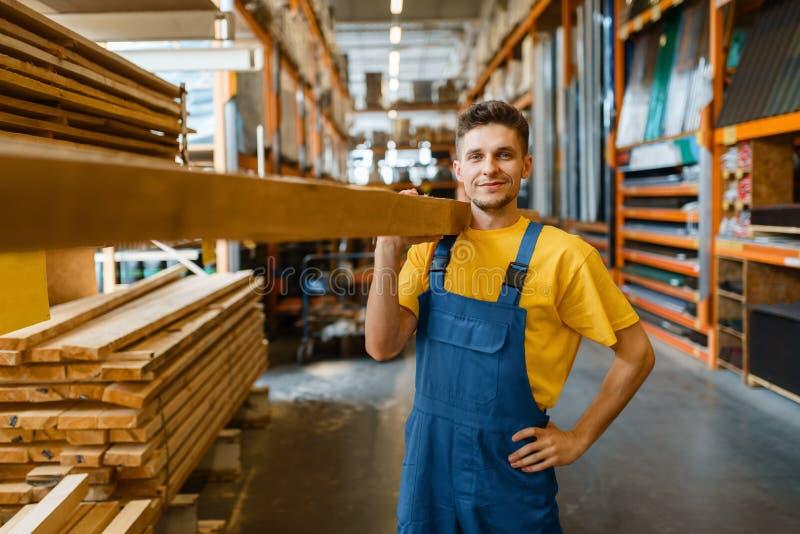 Męski budowniczy przechowuje deski drewniane w sklepie z narzędziami obraz stock